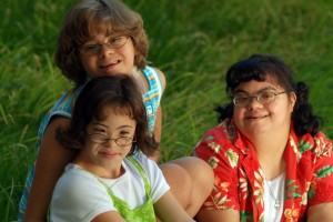 3 young girls with developmental disabilities smiling for the camera