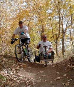 two people nature biking (one using a handcycle)