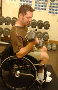 young man using a wheelchair lifts weights at the gym